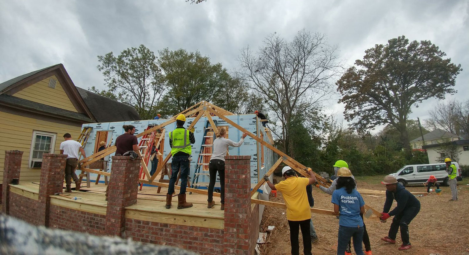 Students helping to install wood beams at Habitat for Humanity project.