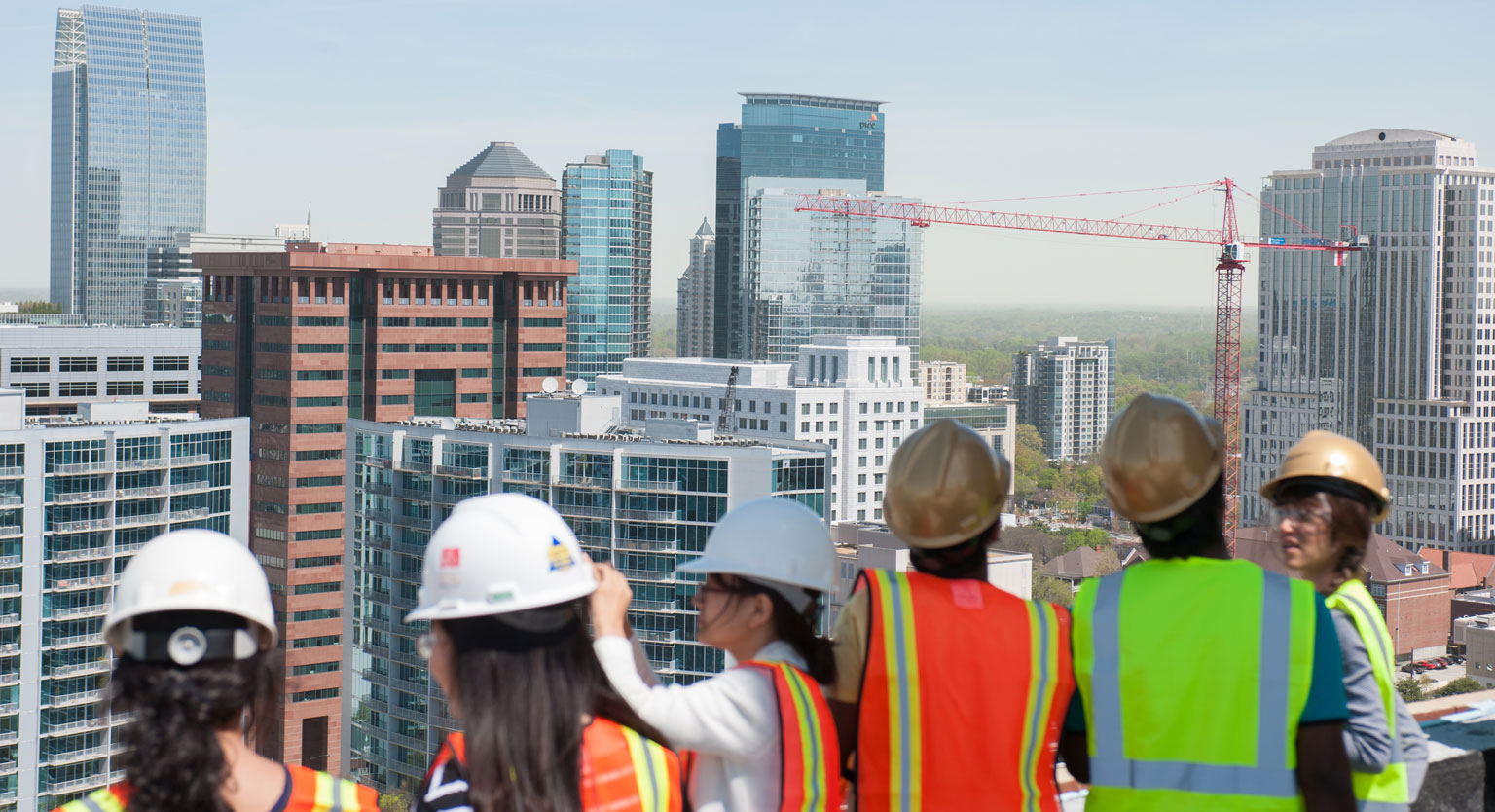 Students looking at a city view from the rooftop of a construction site.