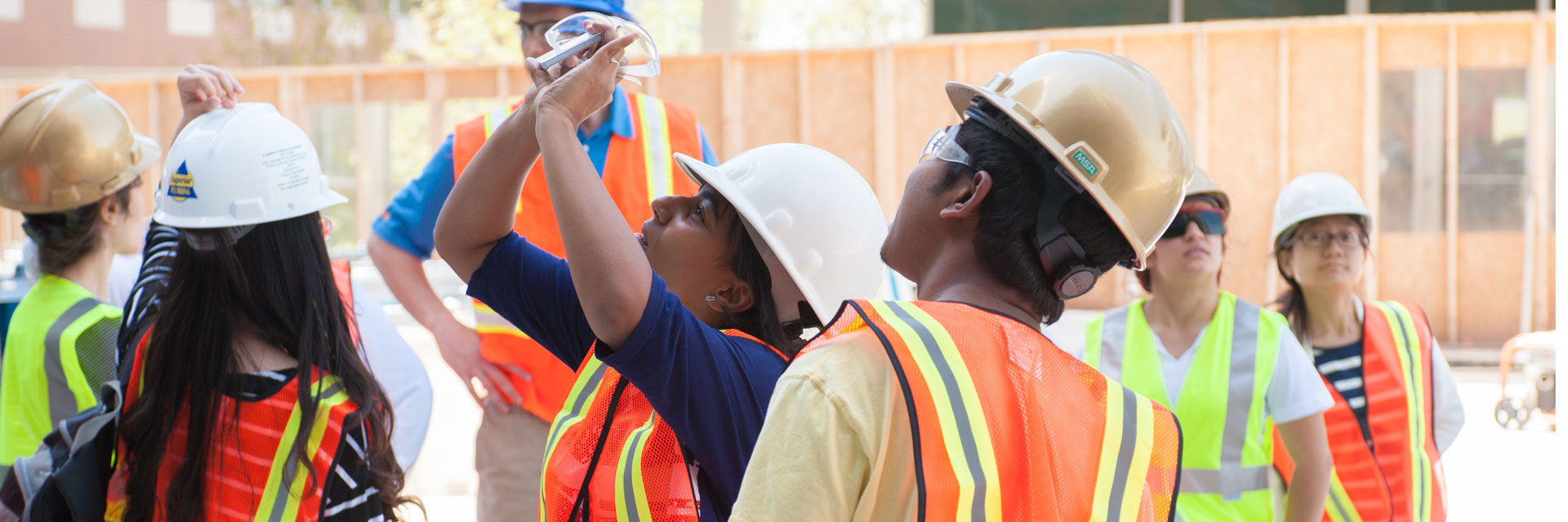 Male and female students observing images through device at construction site.