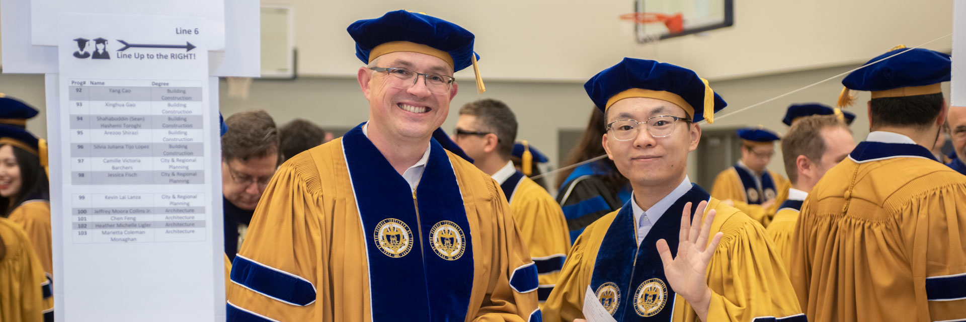 Two Ph.D. graduates standing in line at commencement ceremony. One waving to the camera.