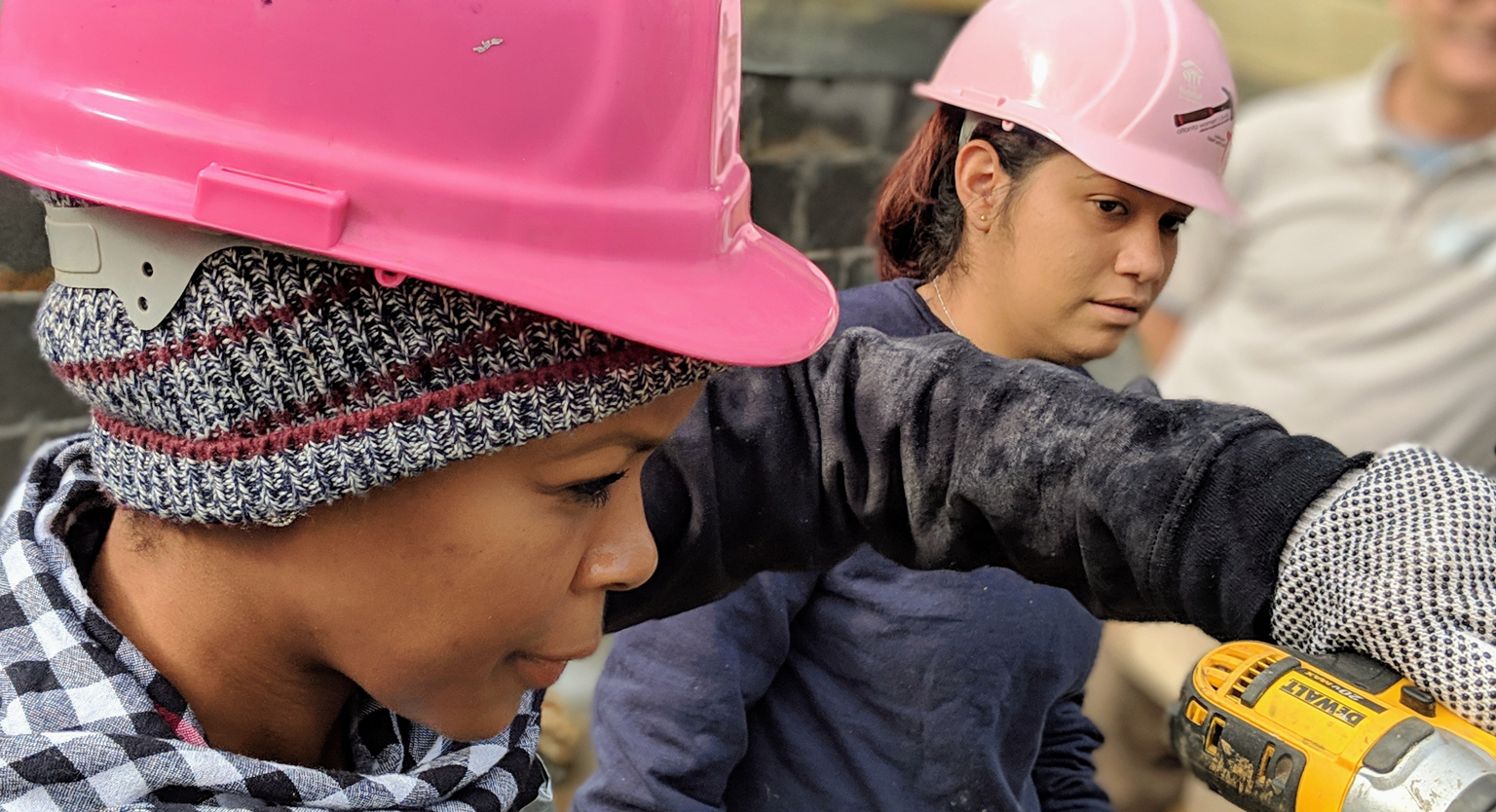Black female student using hand drill at a construction site while a Hispanic female student observes.